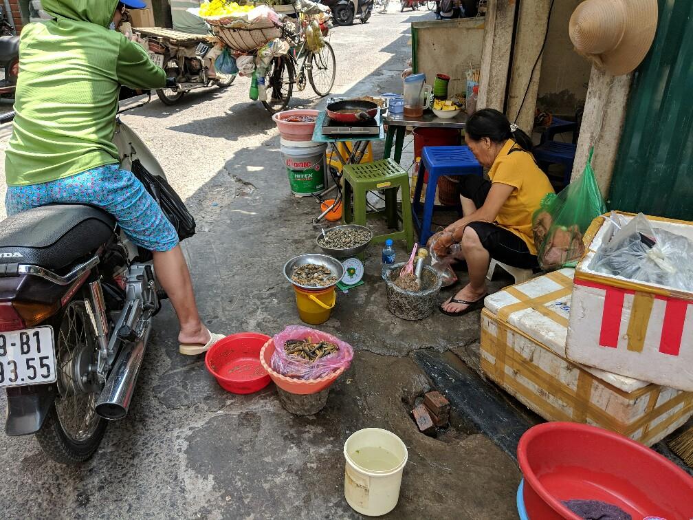 Femme faisant la cuisine dans une rue d'Hanoi