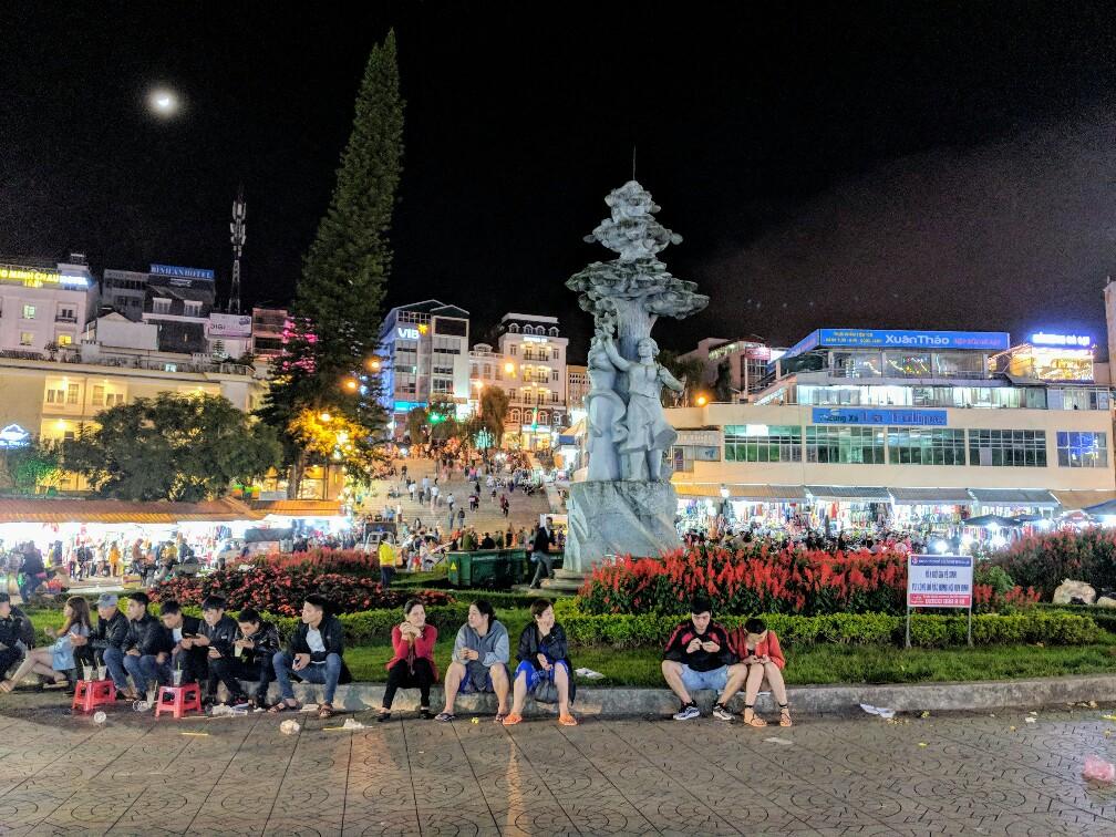 Personnes assises sur la place principale du Marché de nuit de Da Lat