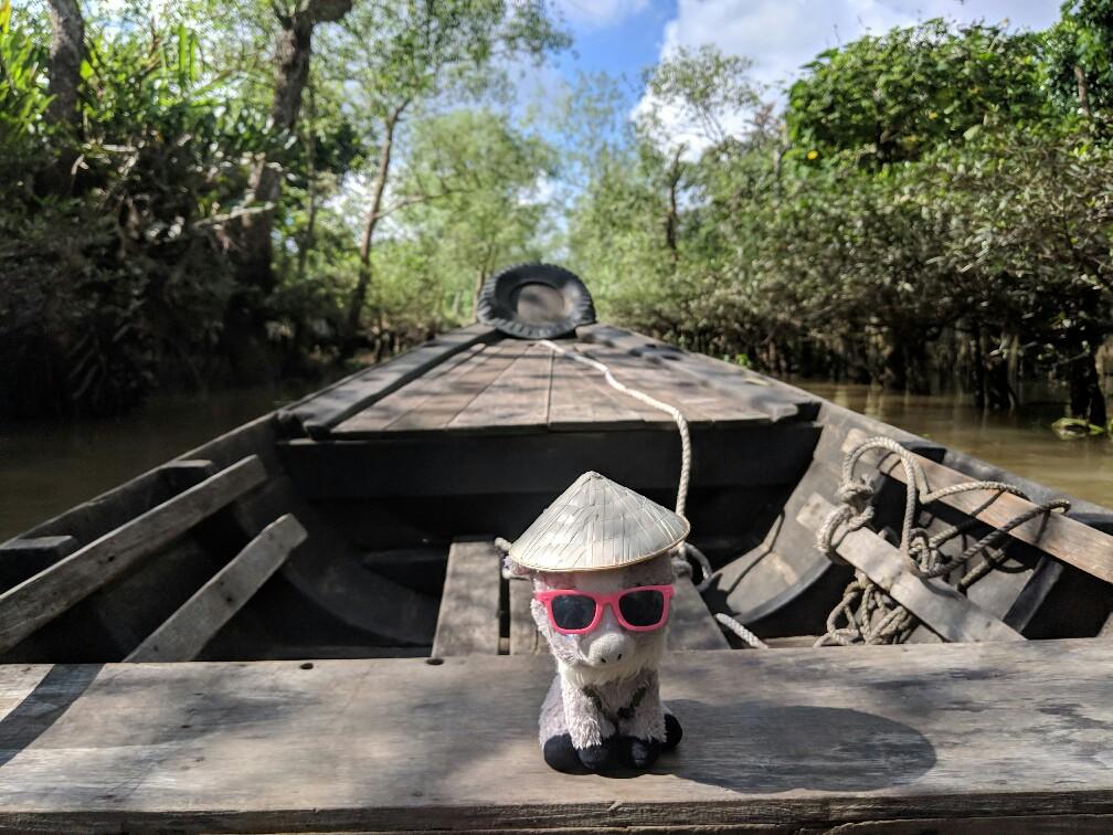 Peluche de Biquette sur la barque dans la jungle du Mekong au Vietnam