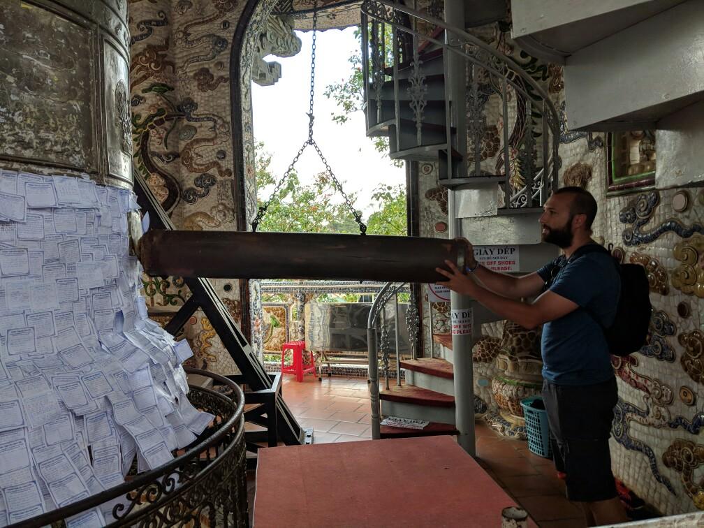 Maniement du rondin pour faire sonner la cloche à la pagode de Linh Phuoc