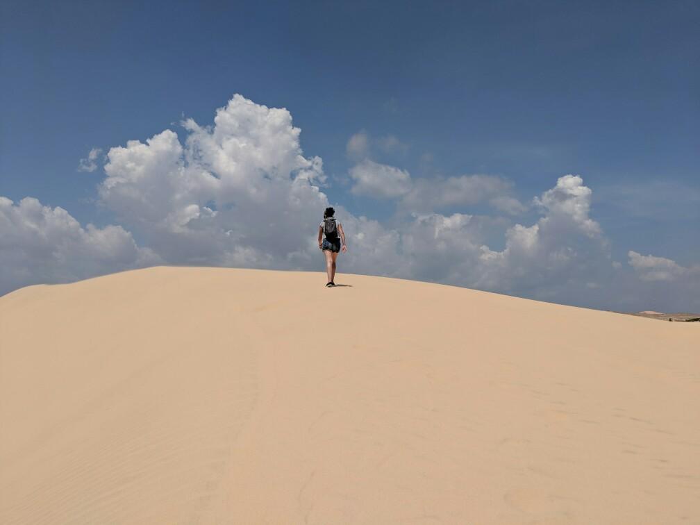 Salomé marche vers le haut de la dune blanche près Mui Ne