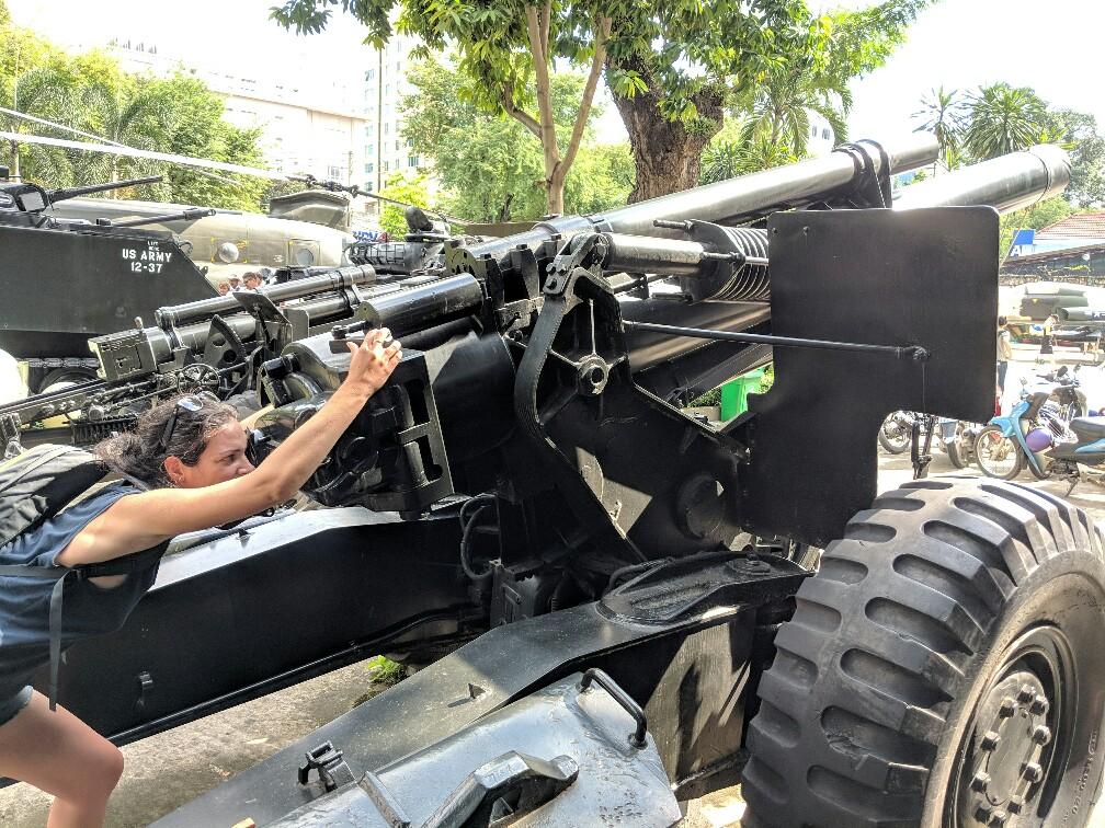 Salomé regarde dans la lunette d'un canon au Musée de la Guerre à Ho Chi Minh, Vietnam
