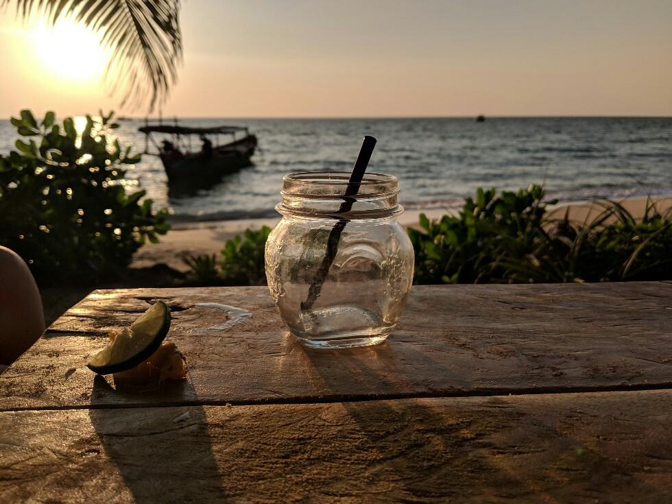 Verre de cocktail vide devant coucher de soleil à Sunset Beach sur Koh Rong Sanloem, Cambodge