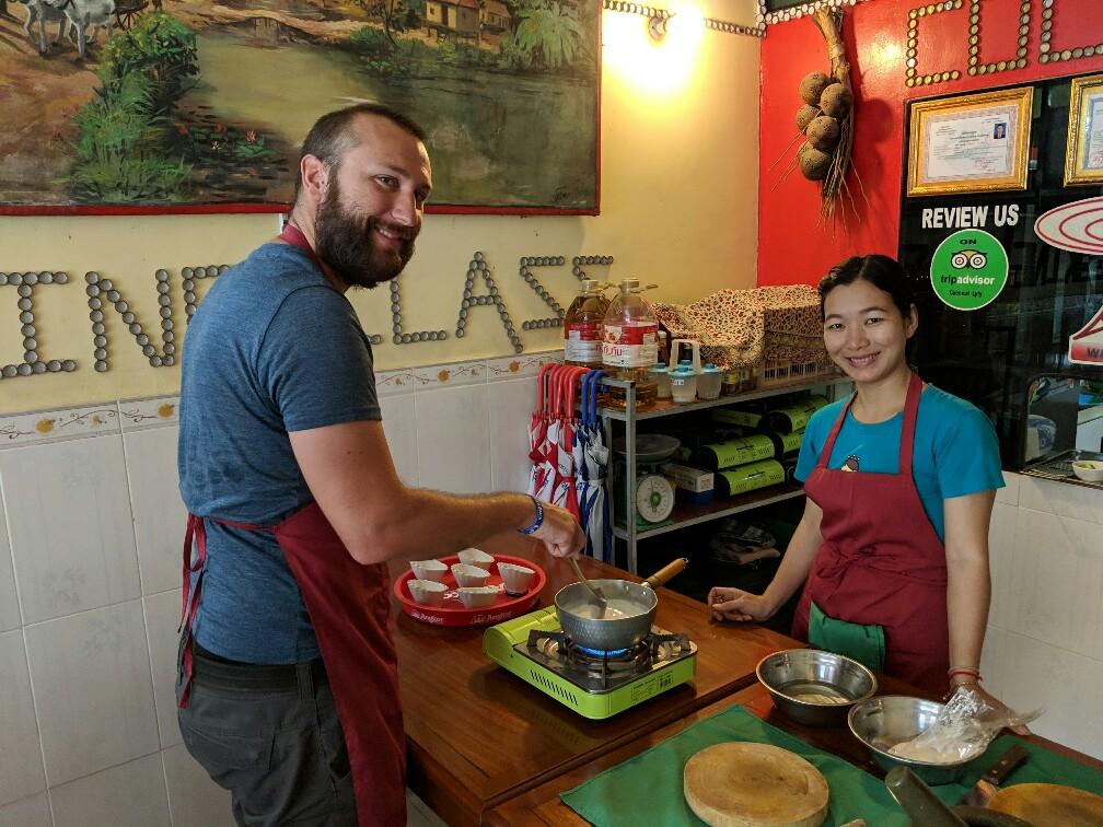 Sylvain touille dans une casserole pendant le cours de cuisine à Battambang