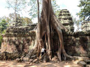 Salomé pose devant de gigantesques racines à Ta Phrom, Cambodge