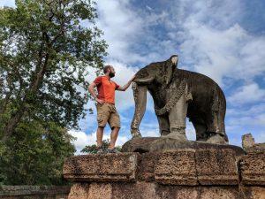 Sylvain carresse la statue d'un éléphant au temple de East Mebon, Cambodge