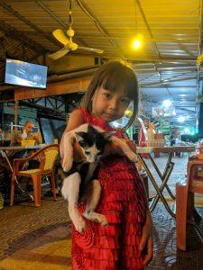 Portrait d'une fillette portant un chaton au marché de nuit de Kampong Cham, Cambodge