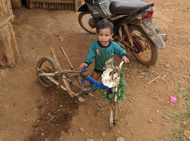 Enfant Bunong joue avec un vélo à moitié détruit, Cambodge
