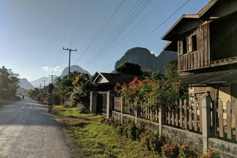 Maisons et fleurs bordent une rue de la banlieue de Vang Vieng, Laos