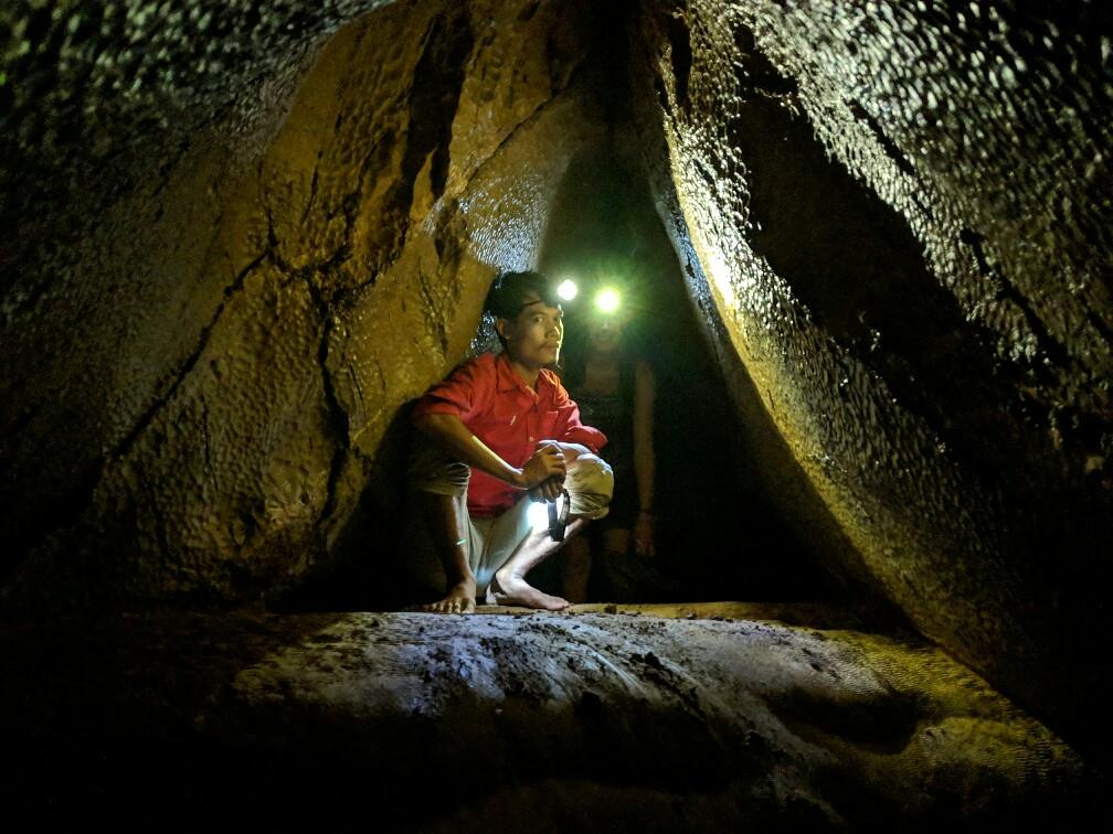 Guide accroupi dans un passage de la grotte de Tham Hoi, Laos