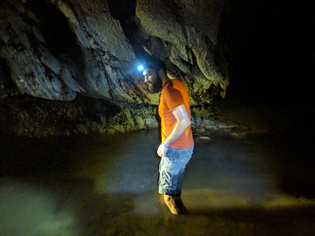 Sylvain progressant dans l'eau de la grotte de Tham Hoi, Laos