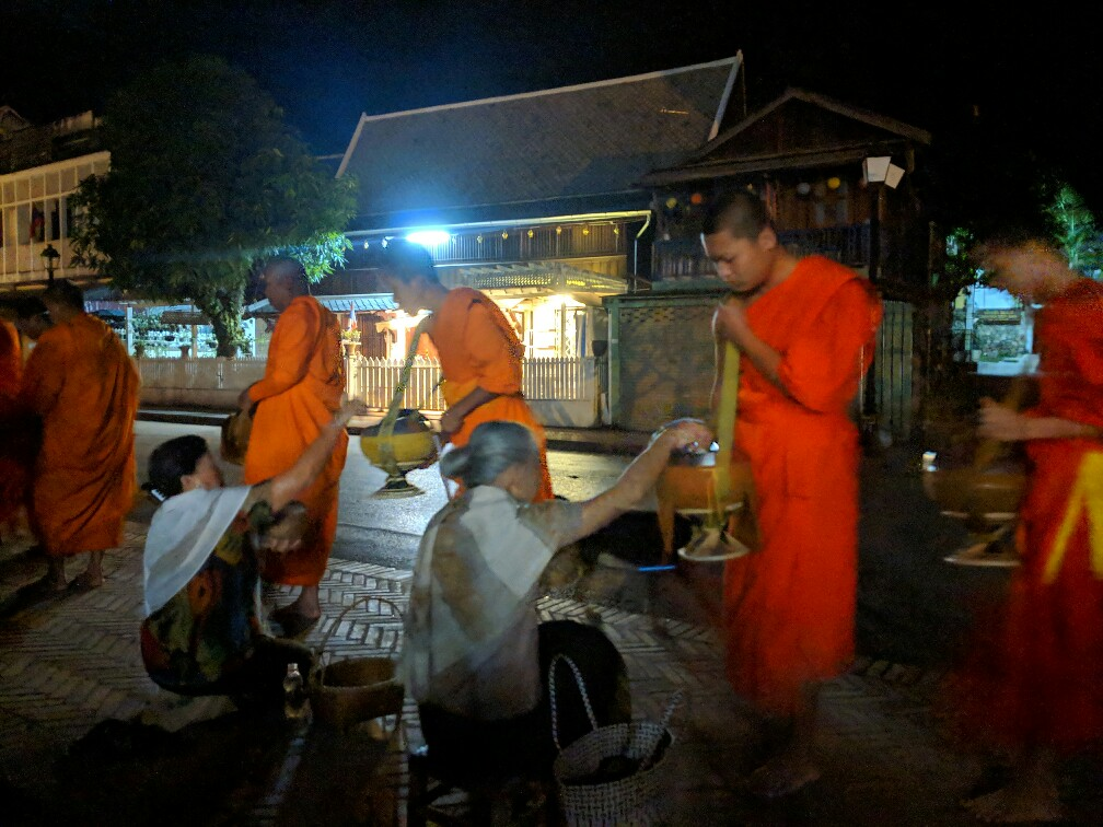 Aumonier donnant à un moine à Luang Prabang, Laos