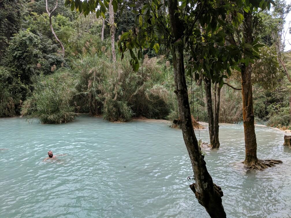 Sylvain se baigne dans l'eau turquoise des chutes de Kuang Si, Laos