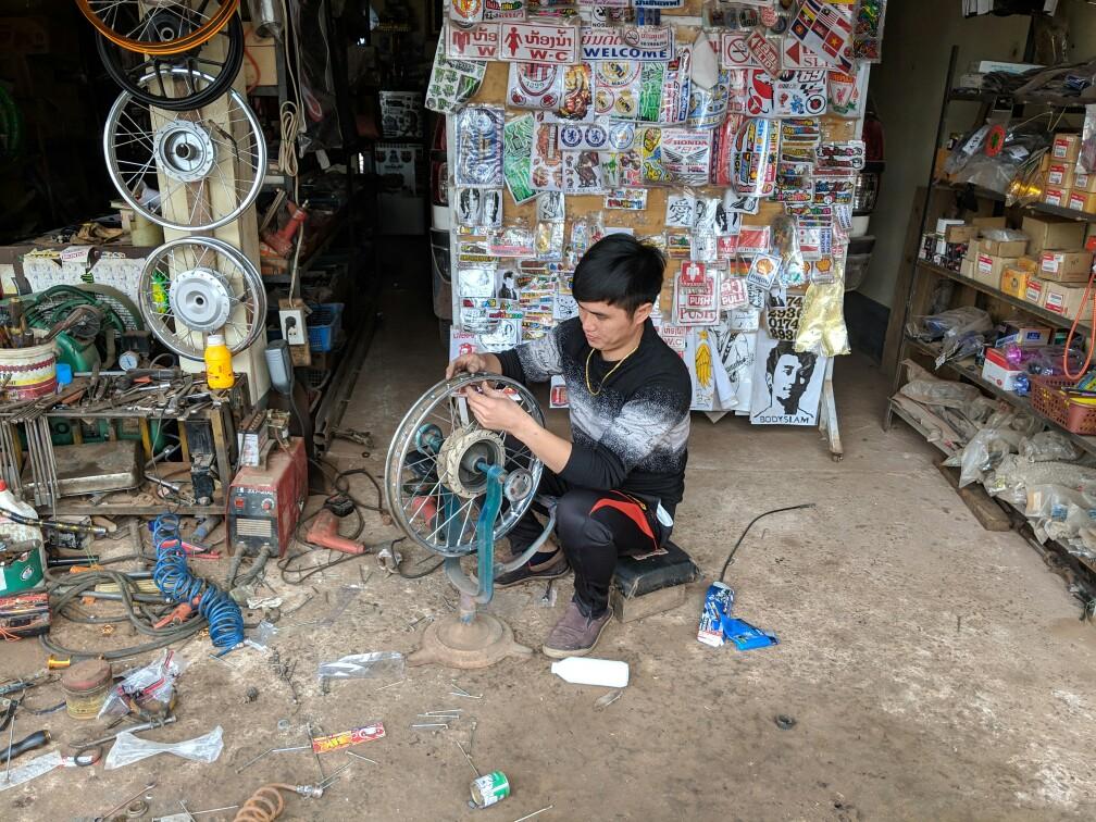 Le mécanicien changent les rayons de la roue près de Luang Namtha au Laos