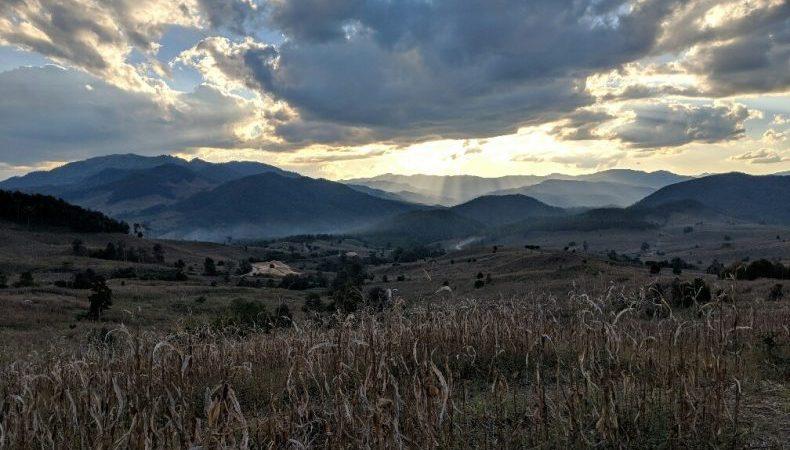 Coucher de soleil sur un champ et des montagnes sur la route vers Mae Chaem, Thailande