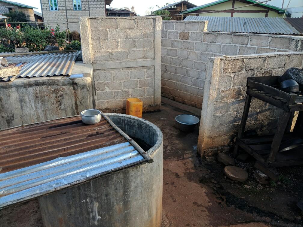 Muret et bassine à côté d'un puit faisant office de salle de bain sur le trek de Kalaw à inle