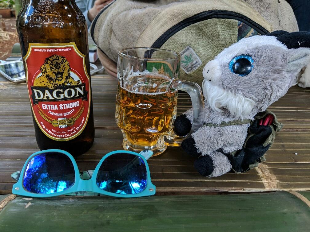 Petite chèvre en peluche sur une table avec un verre de bière