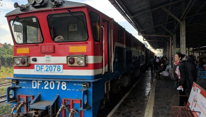 Un train roug et bleu arrive à quai devant Salomé à la gare de Hsipaw, Birmanie