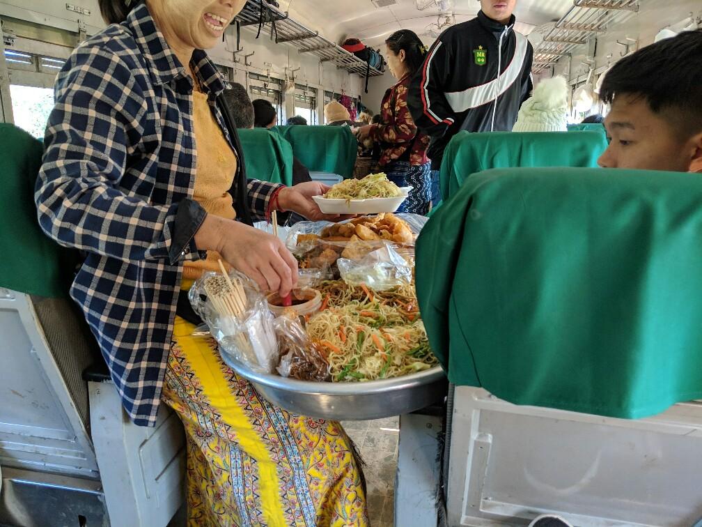 Vendeuse ambulante sert des nouilles à un client dans le train de Hsipaw en Birmanie