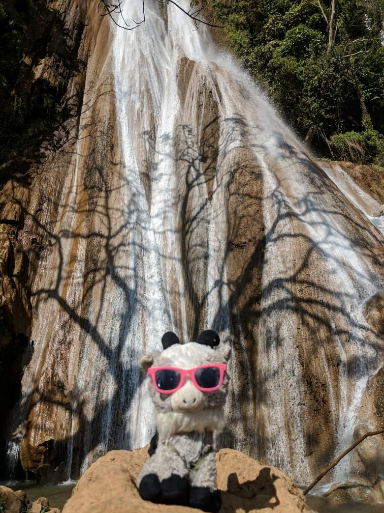 La biquette en peluche pose devant la cascade de Nam Tuk à Hsipaw