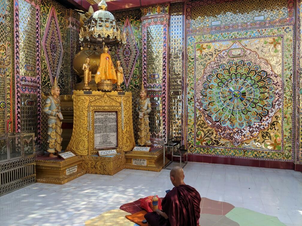 Un moine agenouillé dans un autel regarde son smartphone à la pagode principal de la colline de Mandalay, Birmanie