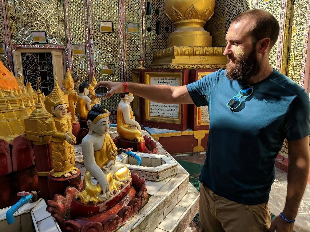 Sylvain arrose la tête d'un petit Bouddha au temple au sommet de la colline de Mandalay, Birmanie