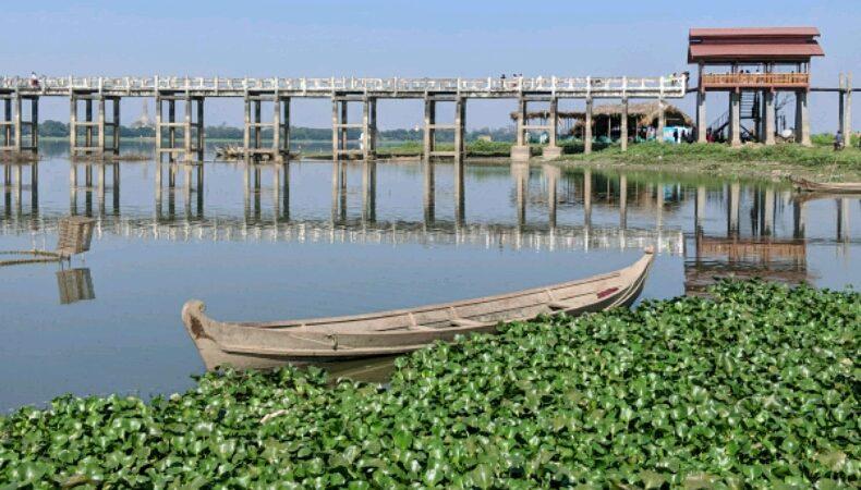 Une barque flotte devant le pont U Bein près de Mandalay, Birmanie