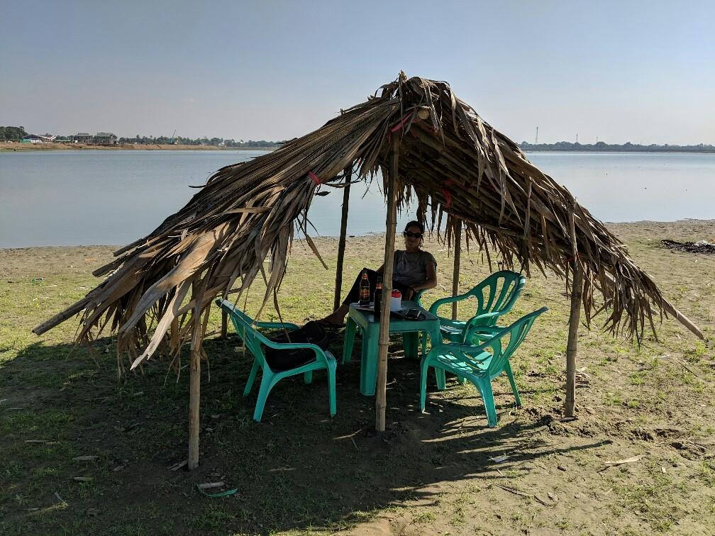 Salomé à l'ombre d'une paillotte près de l'eau au Pont U Bein, Mandalay, Birmanie