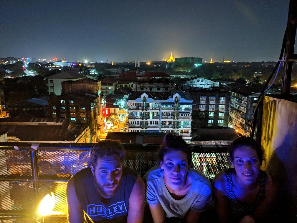 Glenn, Amandine et Salomé sur le rooftop de l'hostel de nuit avec la pagode Shwedagon au loin