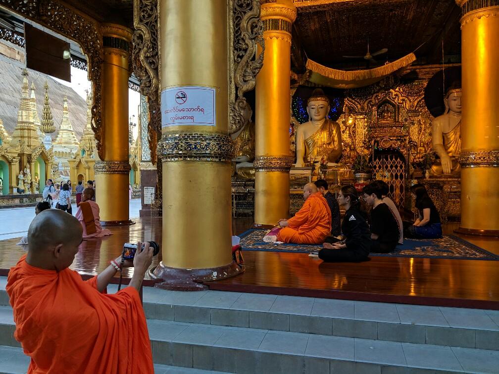 Moine prenant une photo d'un autre moine accroupi en train de prier
