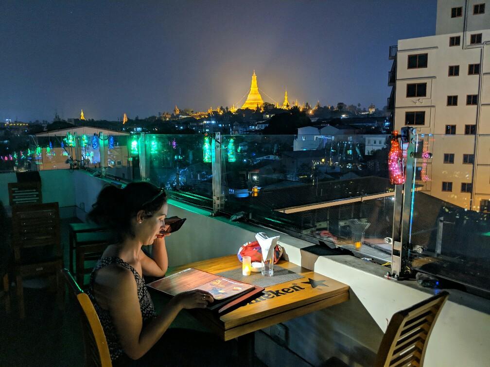 Salomé lisant le menu au rooftop du Vista Bar avec au fond la pagode Shwedagon