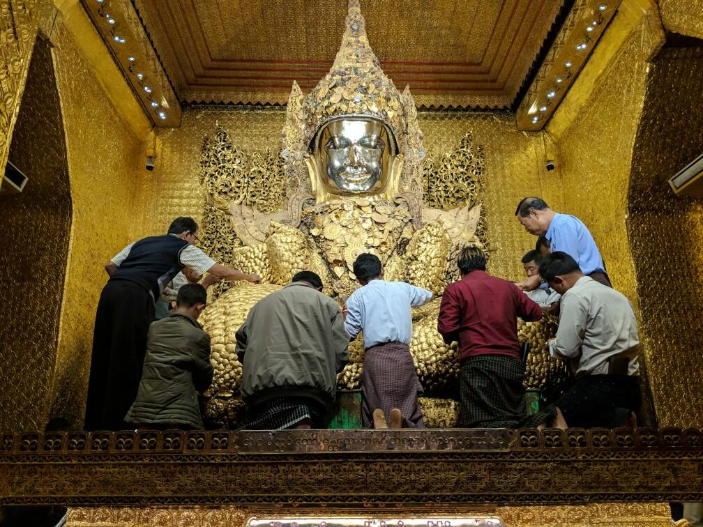 Statue de Bouddha se faisant couvrir de petites feuilles d'or au Temple de Mahamuni, Mandalay, Birmanie