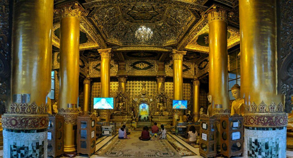 Salle de prière avec des écrans afficant Bouddha sur les côtés