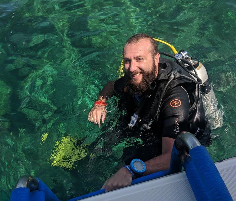 Sylvain au pieds de l'échelle du bateau en tenue de plongée