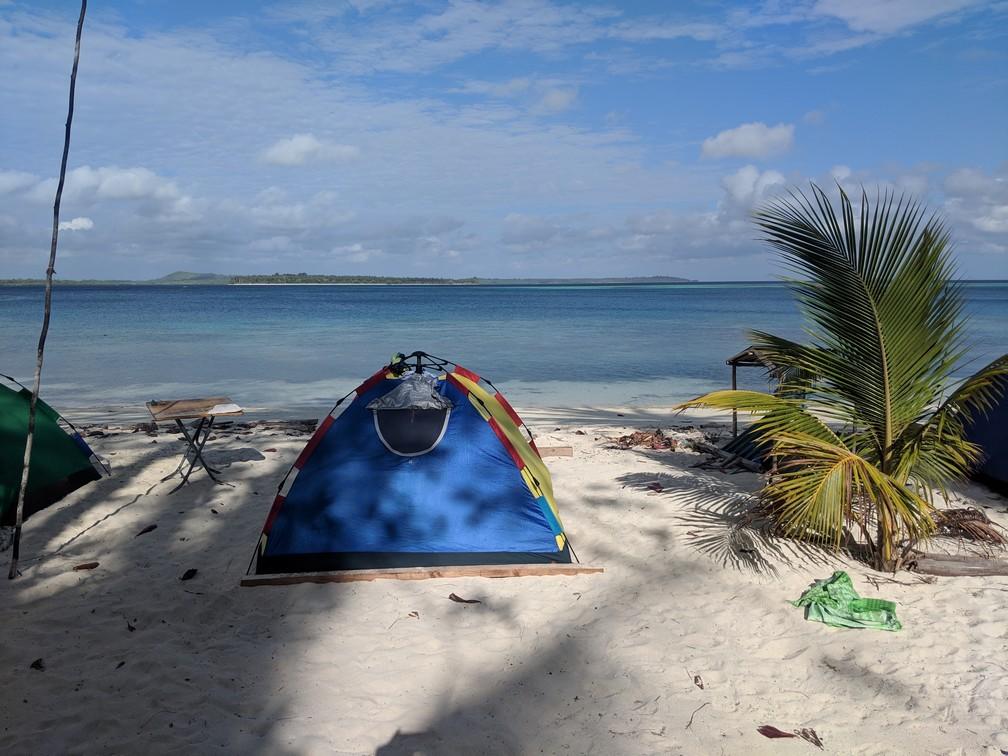 Tente installée sur la plage face à la mer turquoise