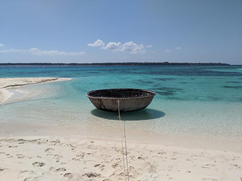 Bateau en forme de coquille de noix flotte au bord de l'eau turquoise près de l'île de Patawan