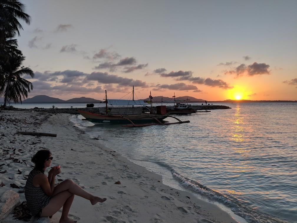 Salomé regarde le coucher de soleil assise sur la plage de l'île de Candaraman