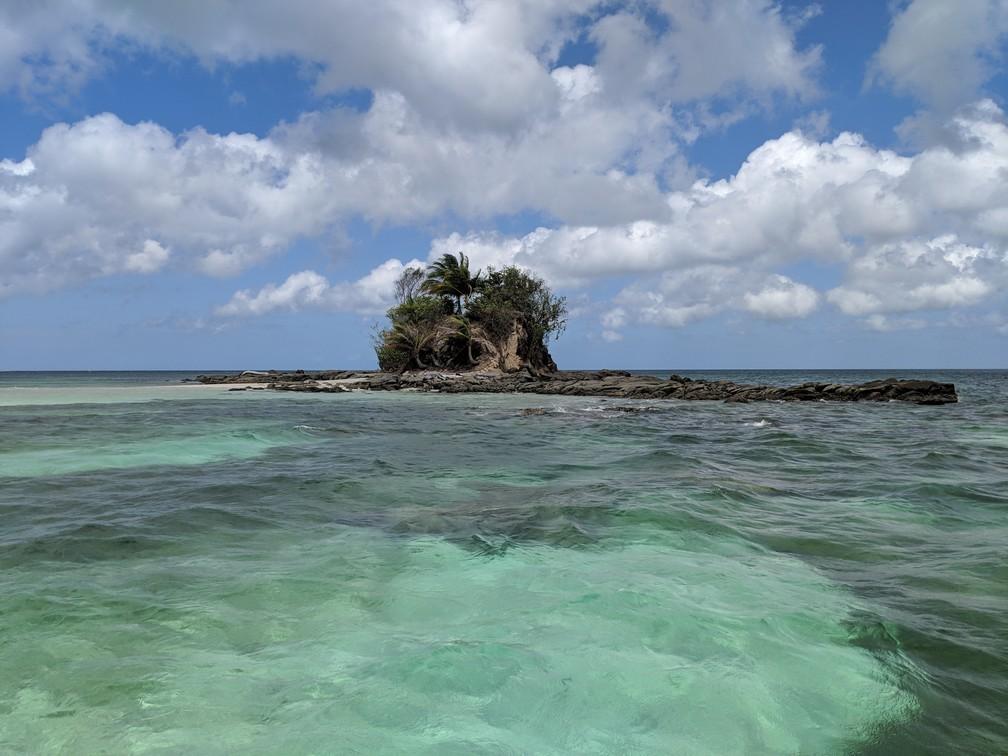 Petite île sans nom vue de loin entourée d'eau turquoise