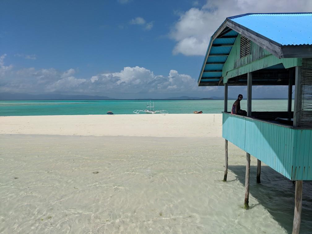Salomé assise au bord d'un abris à Onok island, contemple l'eau transparente sous elle