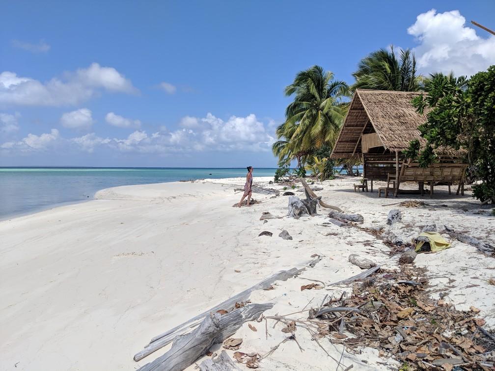 Salomé avance sur la plage vers une cabane de bambou à Onok island