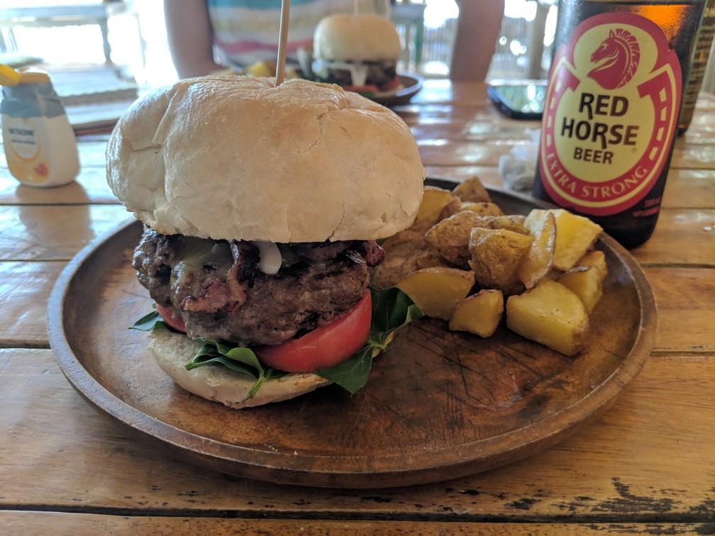 Un gros burger sur une planchette avec des frites maison