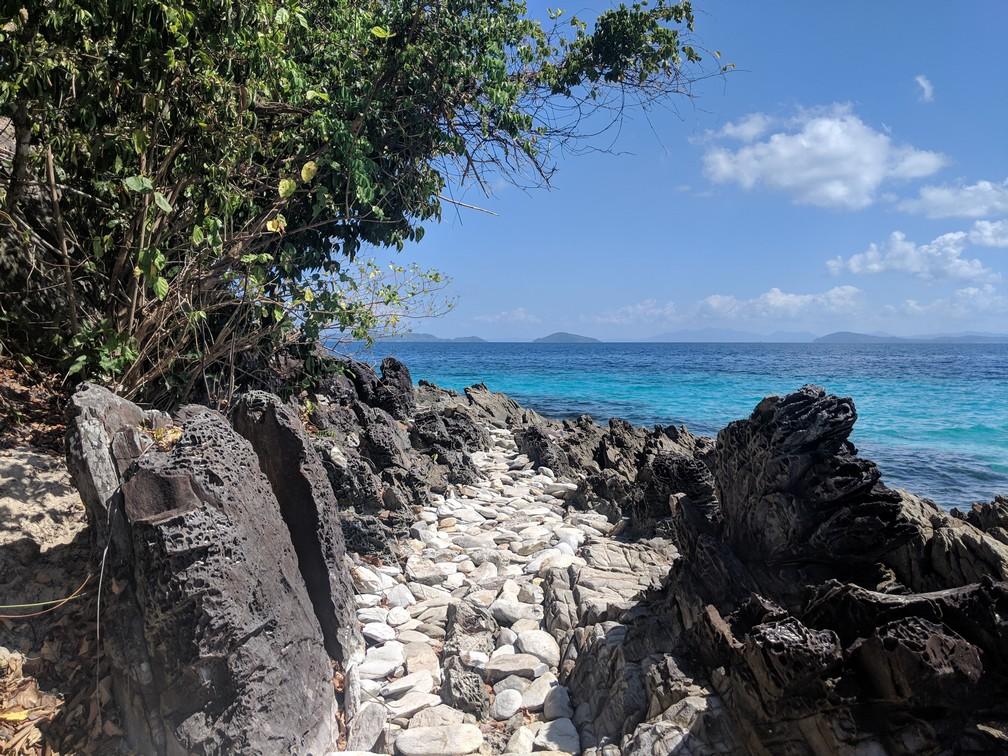 Un chemin de roche blanche semble mener à la mer turquoise
