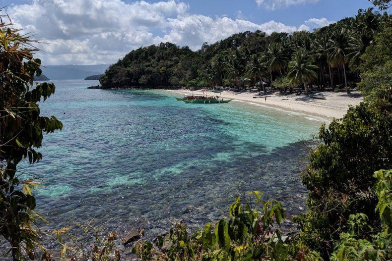 Vue en hauteur d'une baie turquoise avec une banca au bord de la plage