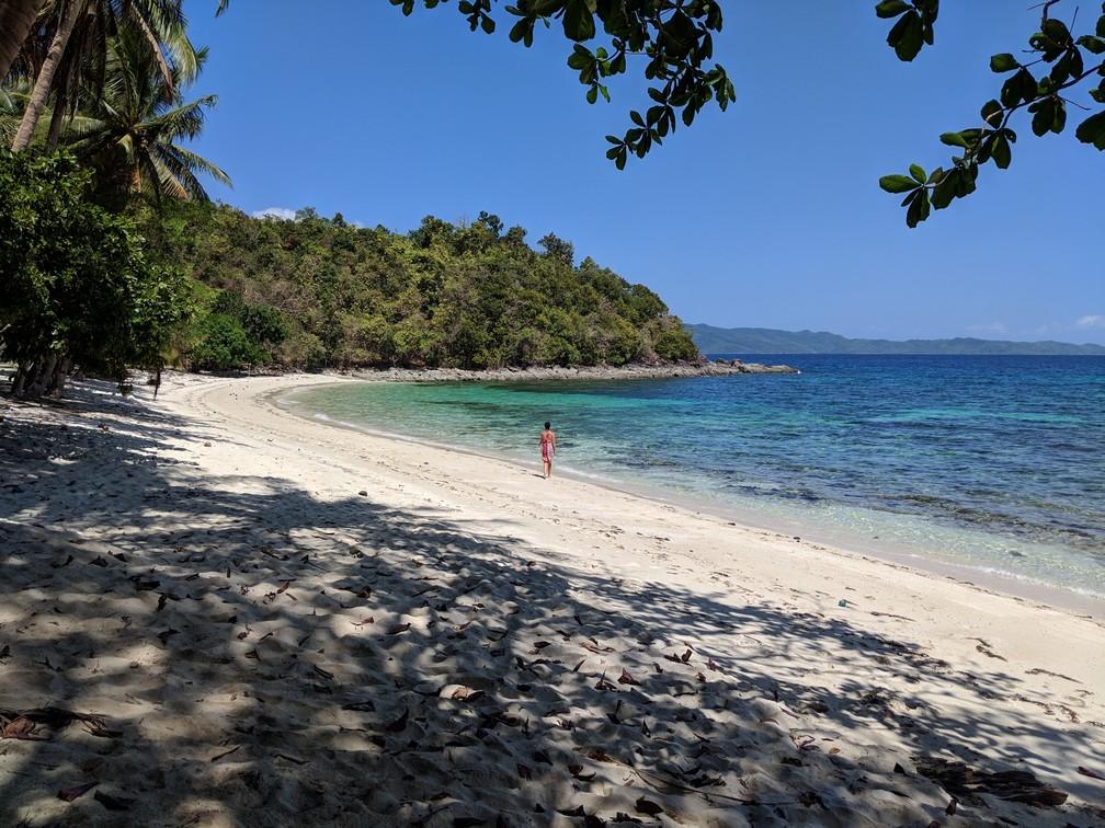 Salomé se balade le long de l'eau turquoise sur une plage déserte