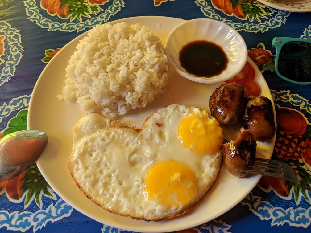Une assiette avec des morceaux de saucisse, deux oeufs au plat en forme de coeur et du riz