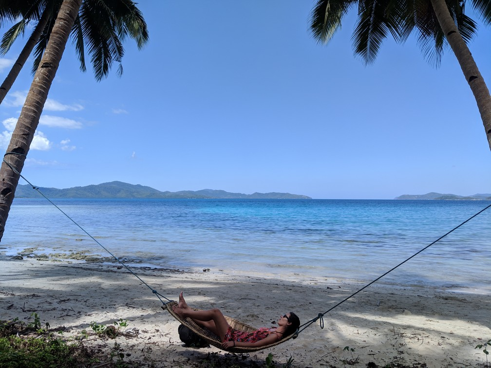Salomé est allongée dans un hamac étendu entre deux cocotiers immenses, la mer en arrière-plan