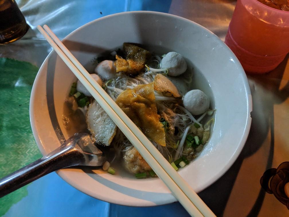 Un bol de soupe de nouilles avec des boulettes de porc, des morceaux de porc et quelques légumes