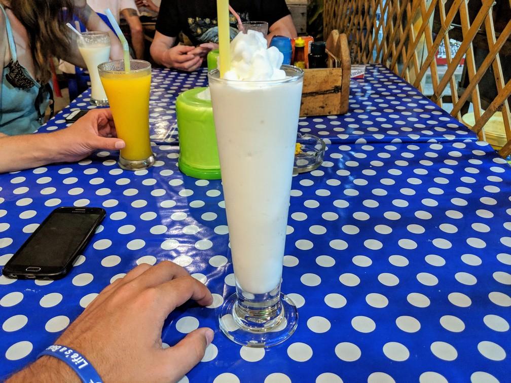 Un coconut shake dans un grand verre posé sur la table du restaurant