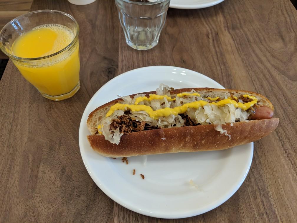 Un beau hotdog avec de la moutarde sur une assiette avec un verre de jus d'orange
