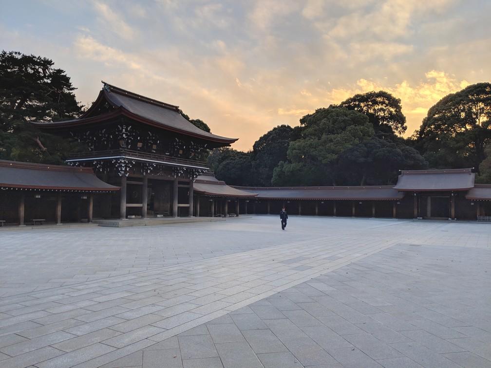 Gardien marchant seul dans la cour du Sanctuaire Meiji-Jingu, coucher de soleil derrière